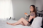 boudoir photo of woman in bed drinking coffee & eating douhgnut