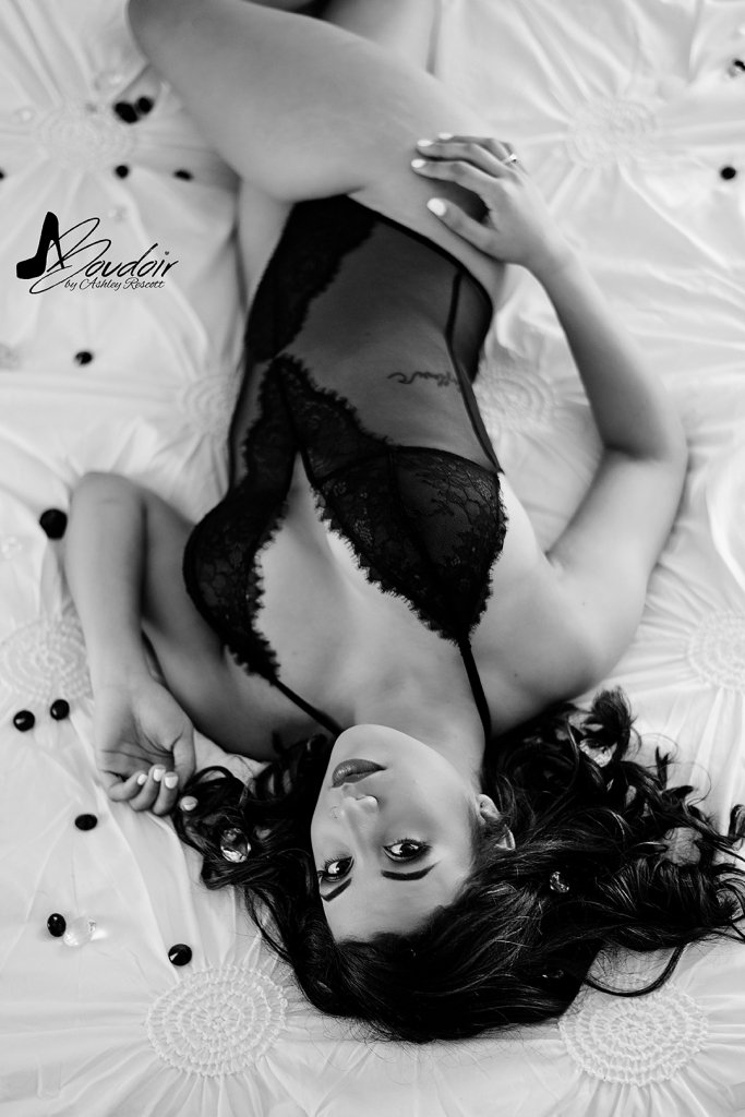 black and white image of woman lying in bed surrounded by gems