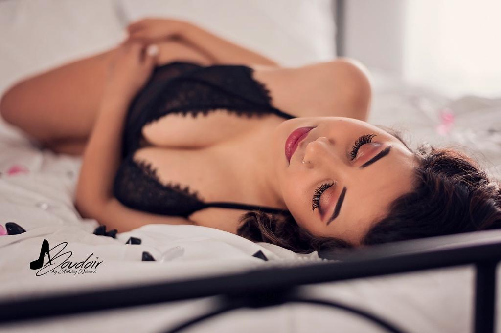 woman in black teddy lying on bed