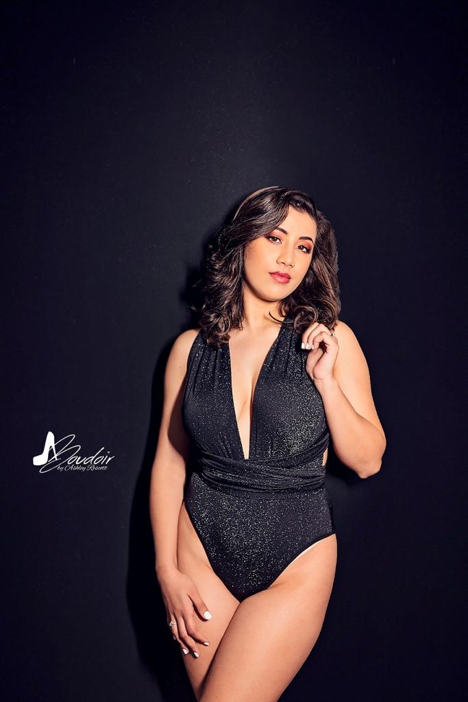 woman in bodysuit on black wall