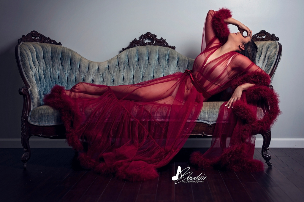 woman in red robe reclining on couch