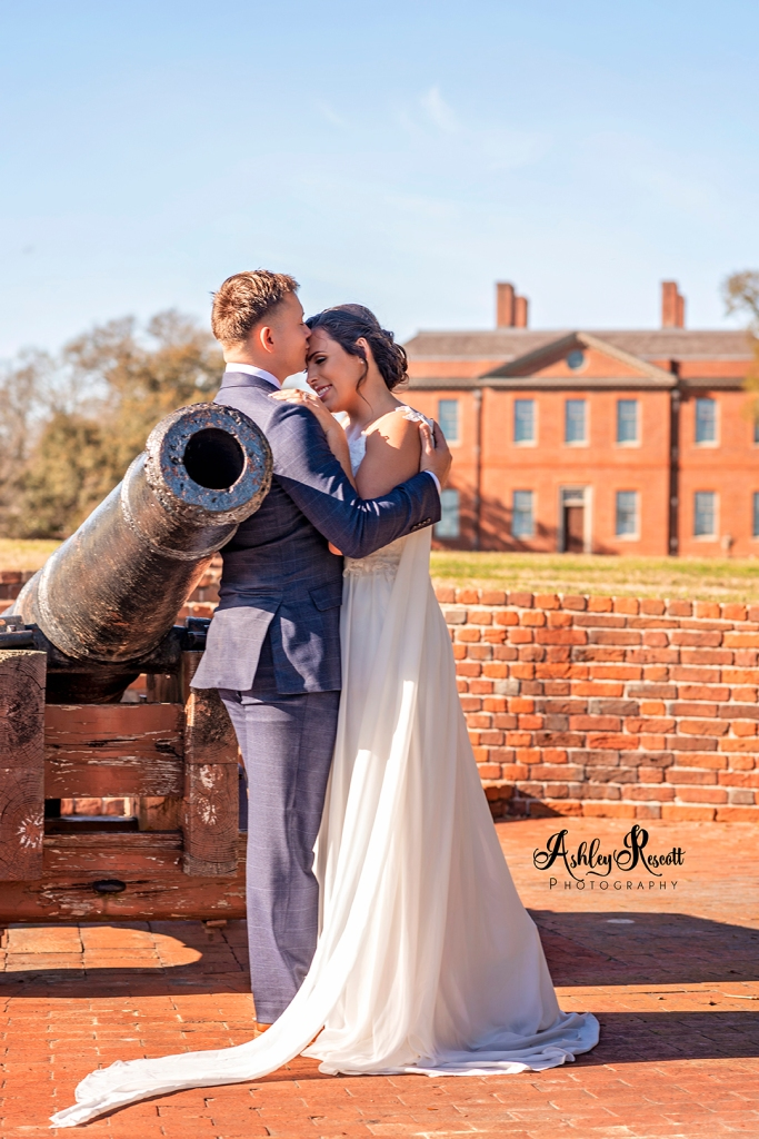 Groom holding bride while leaning against cannon behind the palace