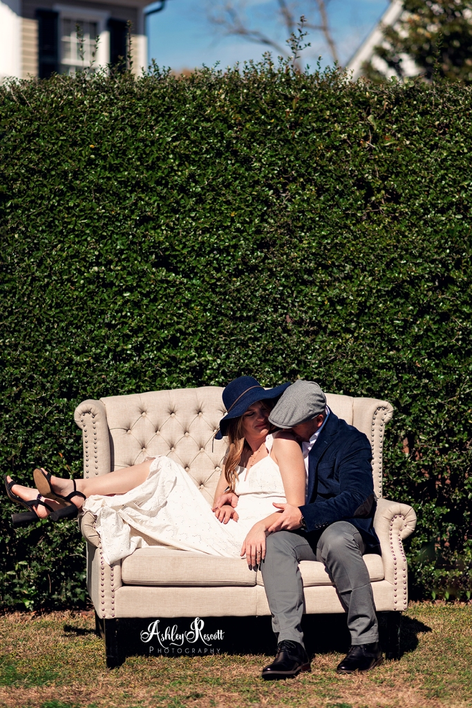 couple on couch in front of tall hedge while canoodling