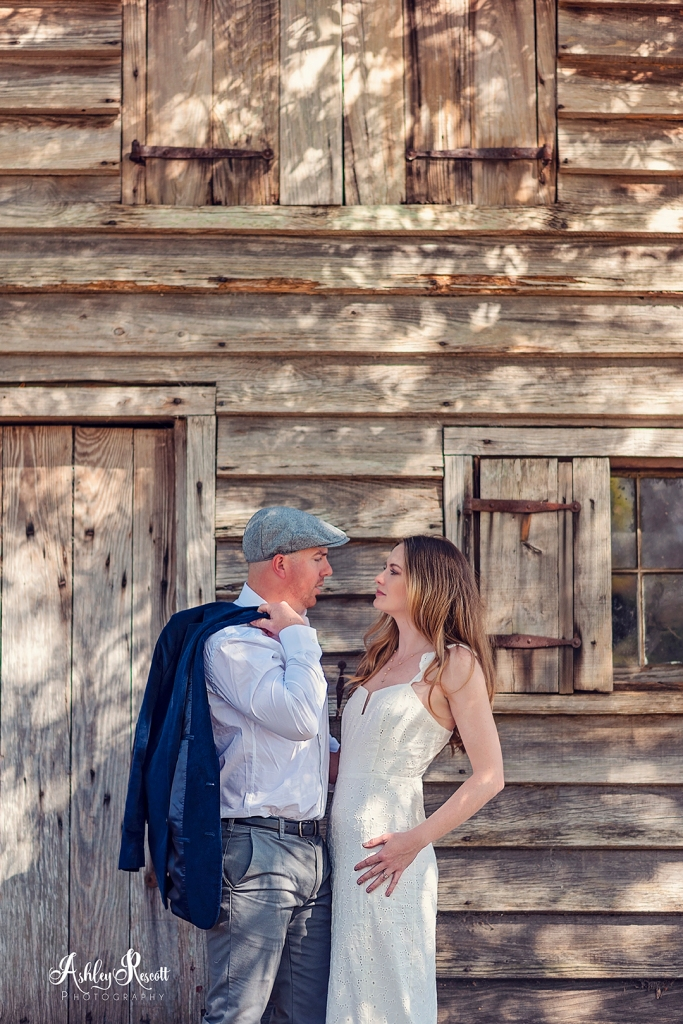 couple in front of wooden building in dappled light