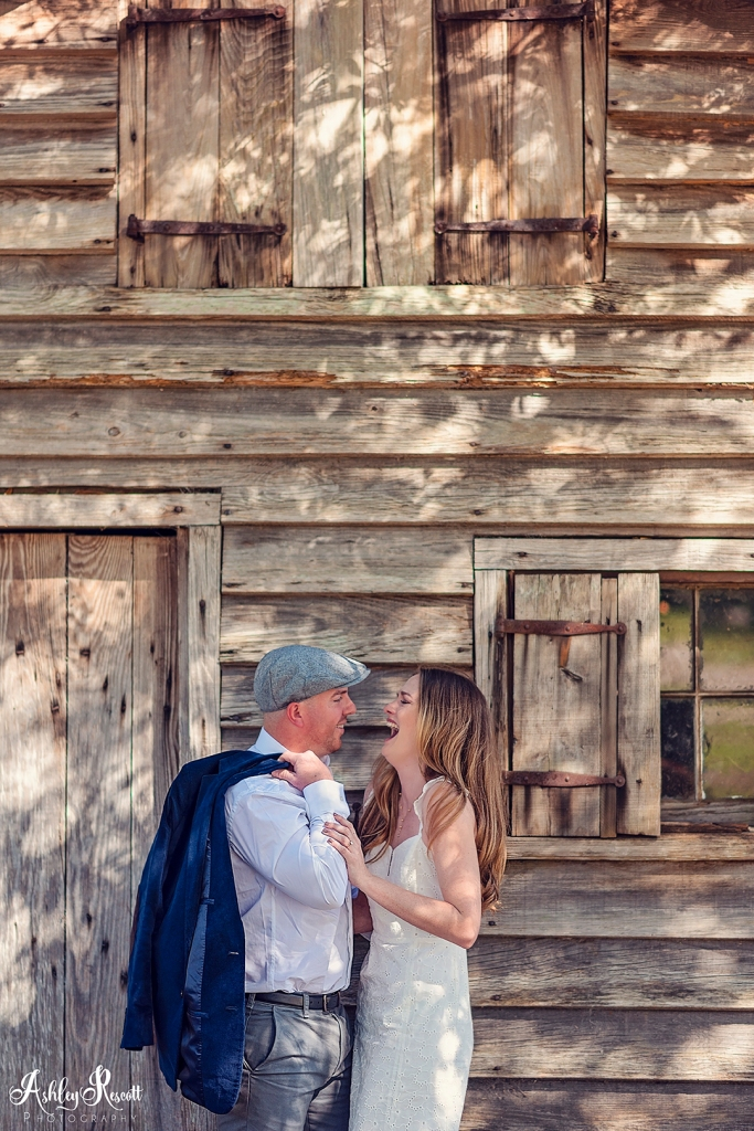 engaged couple laughing in front of cabin
