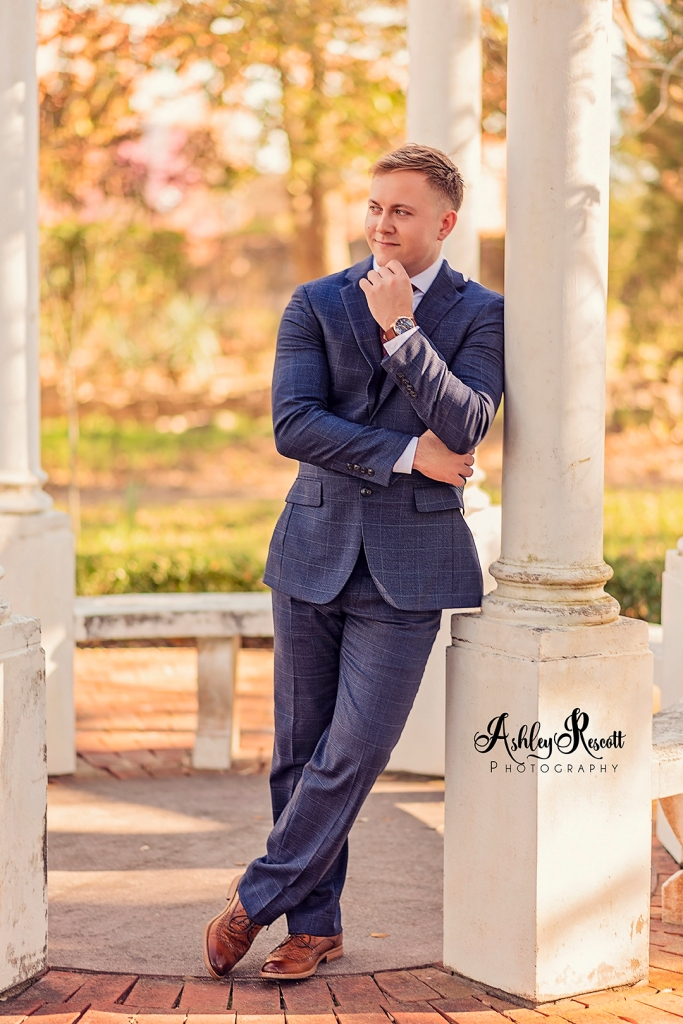 Groom leaning against gazebo