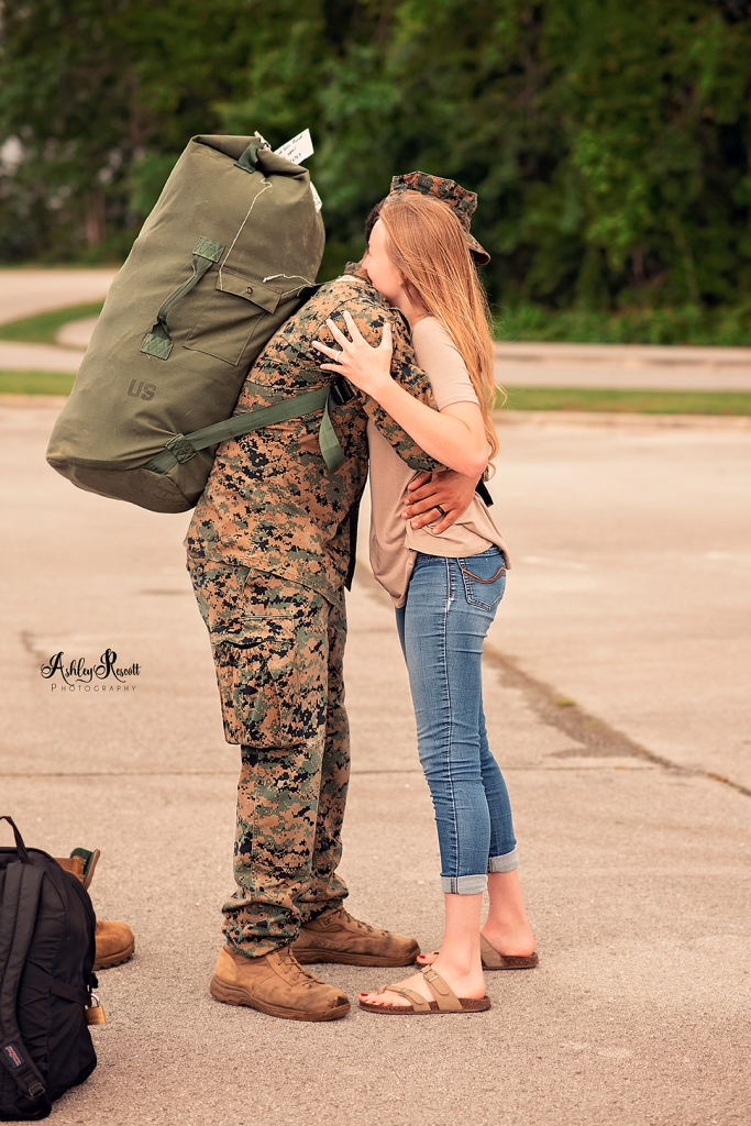 marine hugging his wife with backpack