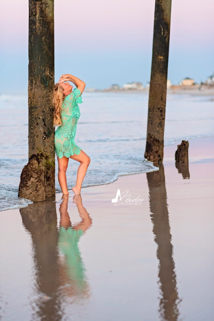 woman leaning against pier and reflected in water