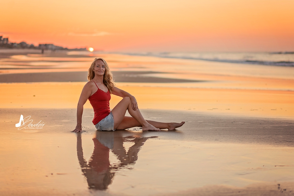 woman sitting on beach with reflection