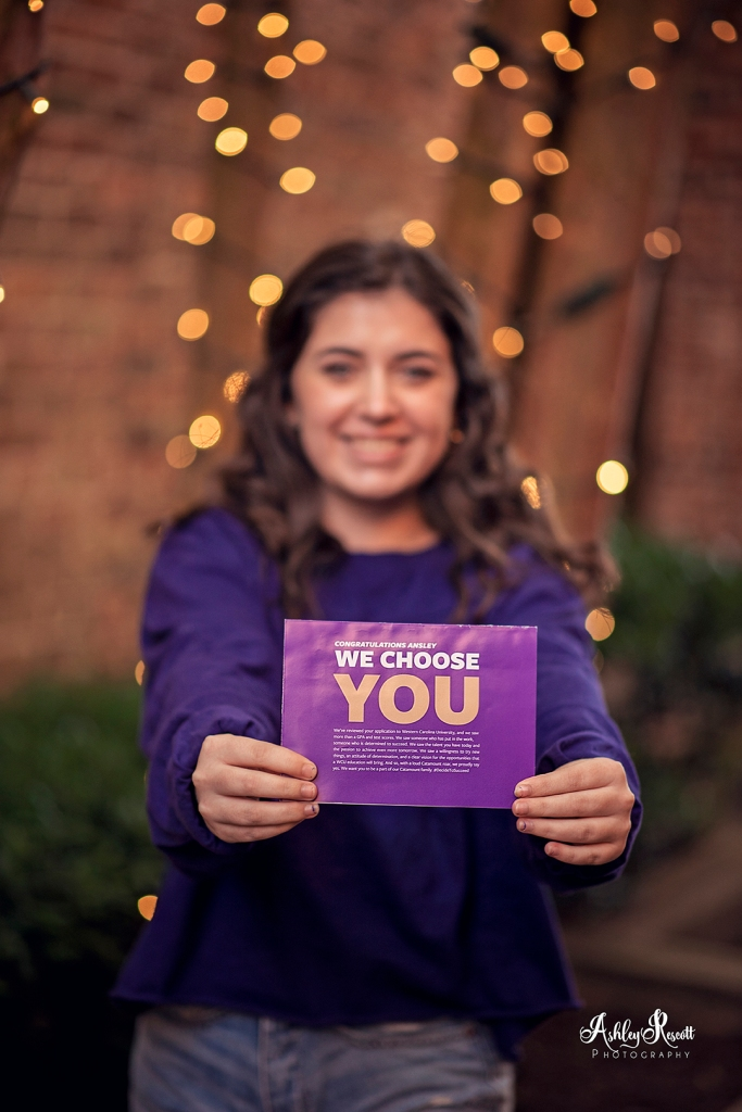 teen girl holding college acceptance letter