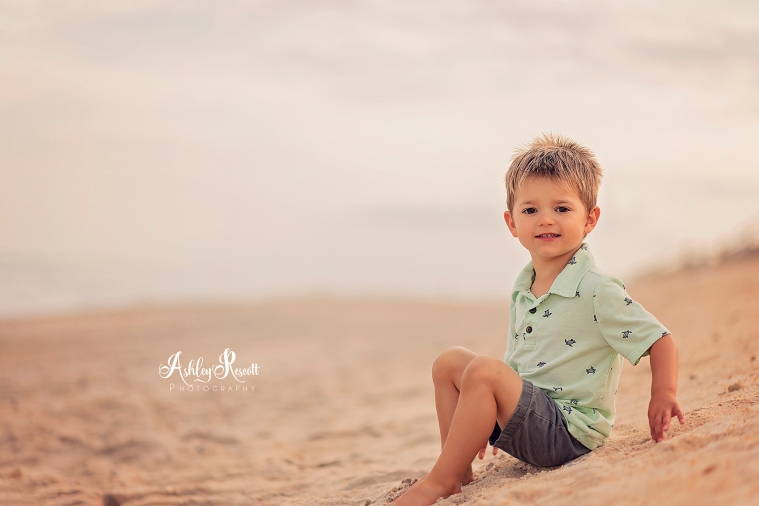 little boy sitting in sand on beach