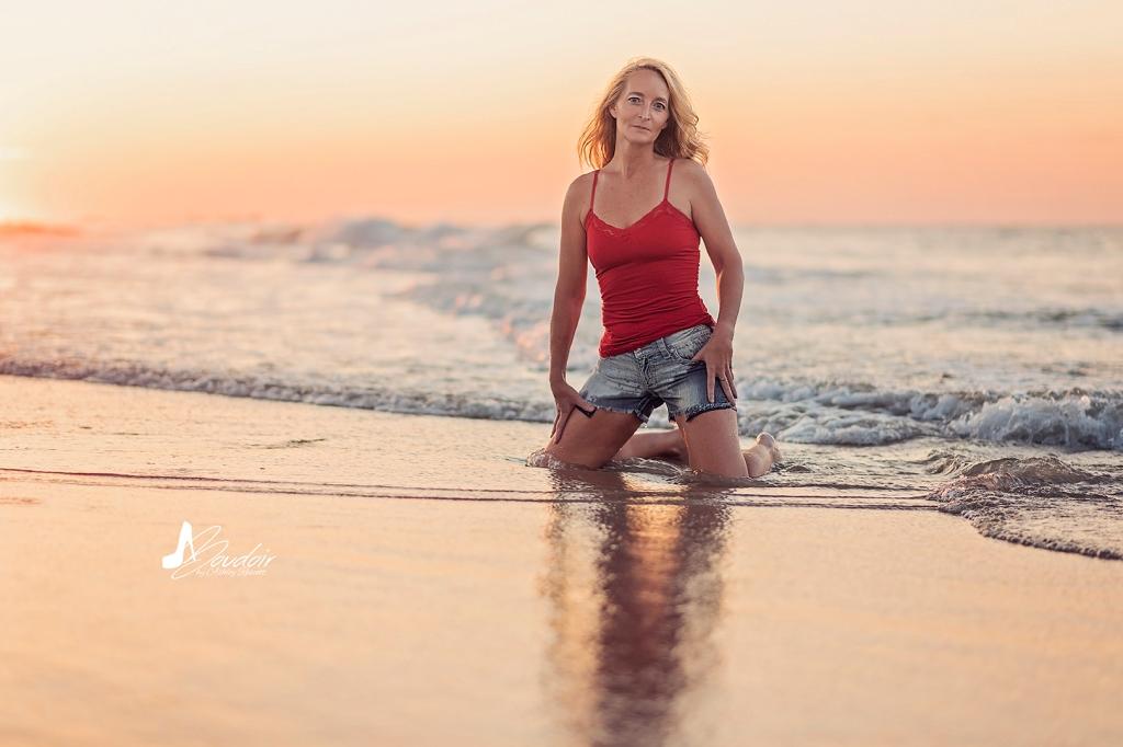 woman kneeling in water on beach