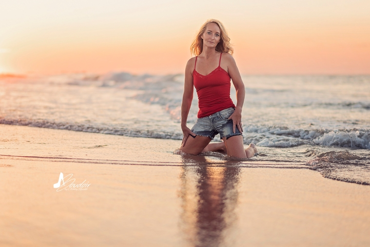 woman kneeling in water on beach