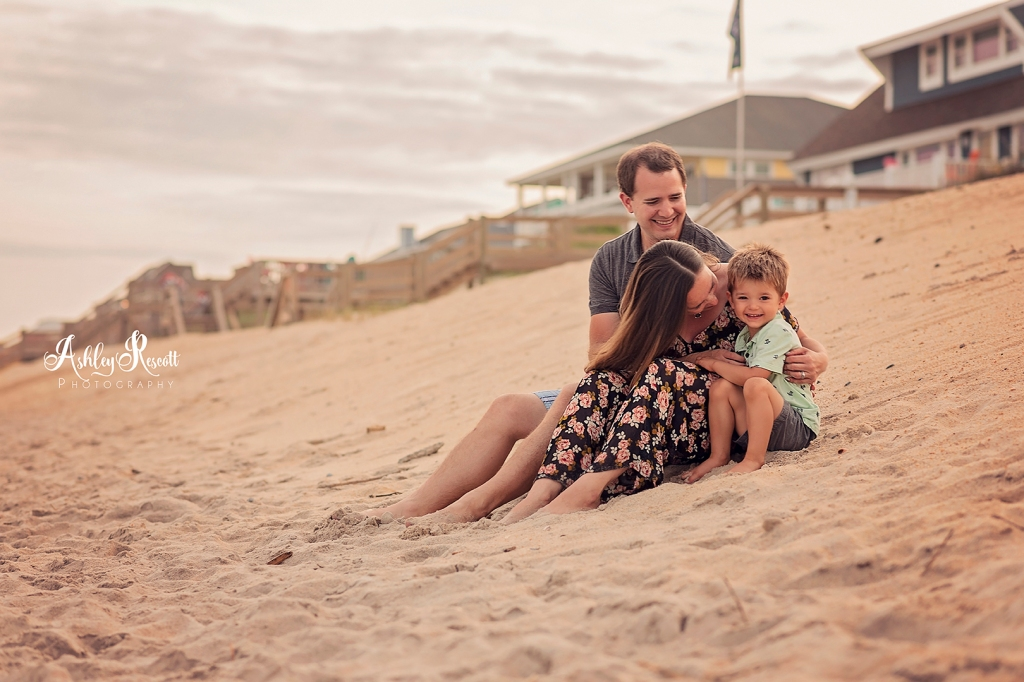 family sitting in sand on beach