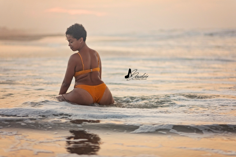 woman sitting in water on beach