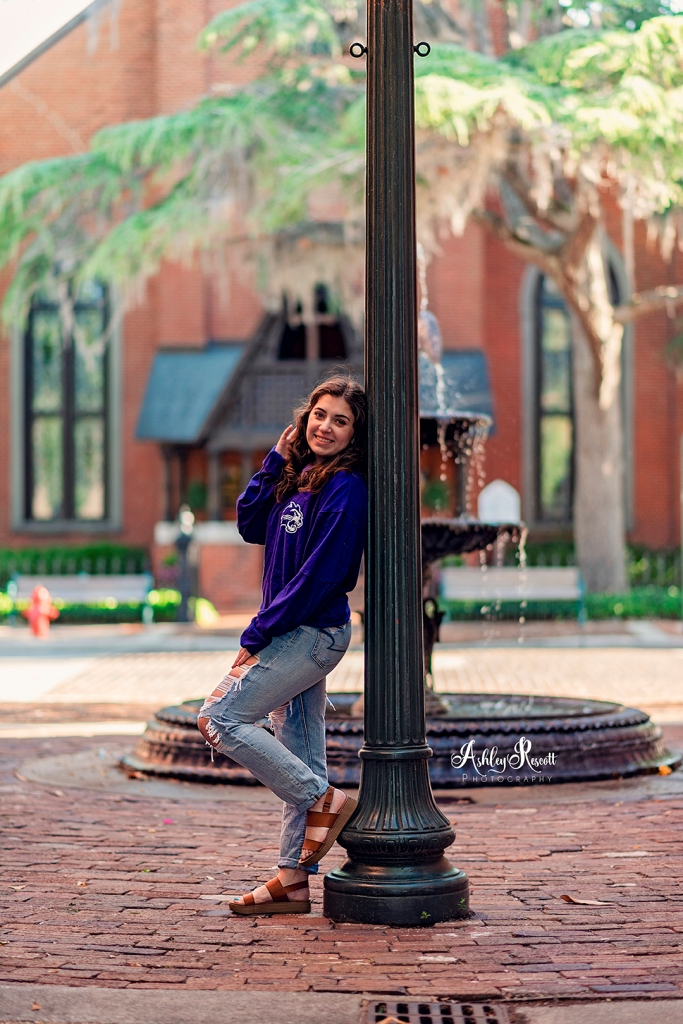 senior girl leaning on lamp post near fountain