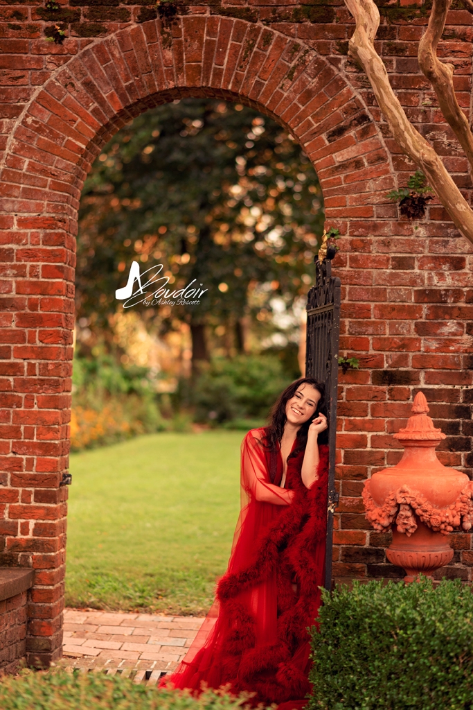 woman wearing red robe in garden gateway