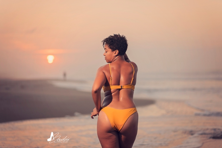woman standing on beach looking over shoulder at sunrise