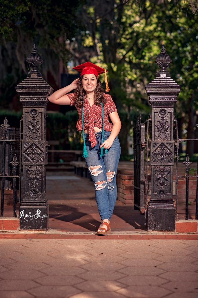senior girl with tassels & cap standing in gateway