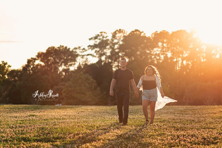 couple holding hands while walking through a field