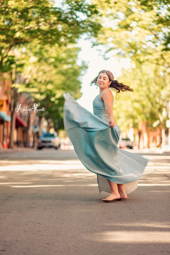 teen girl in blue gown spinning in street