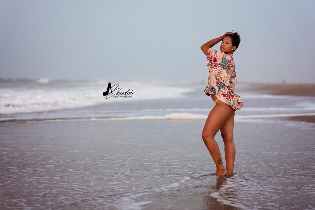 woman in shirt and bikini in water on beach