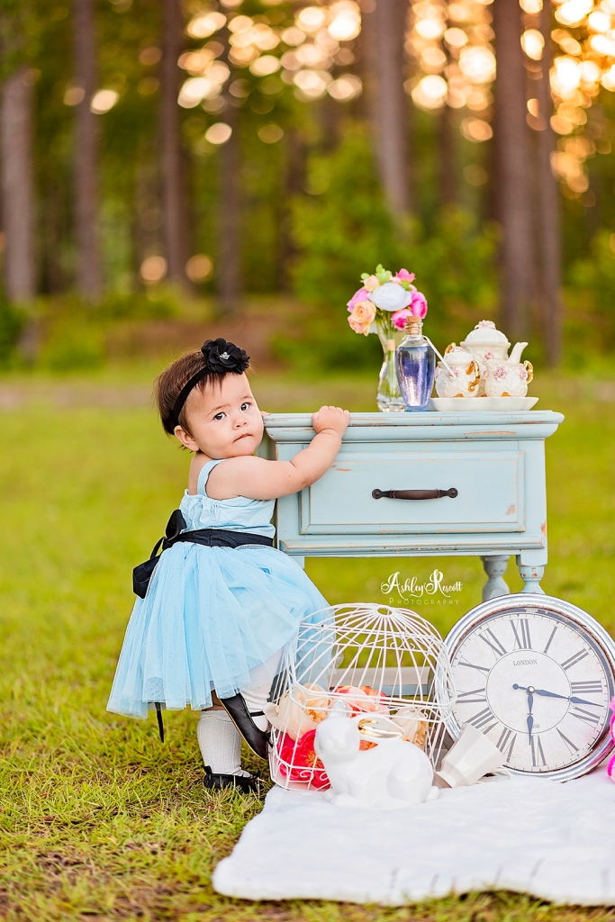toddler dressed as alice standing holding onto table