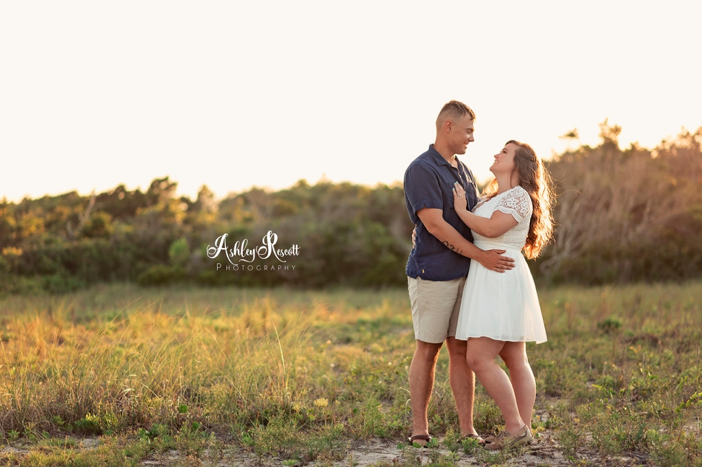 couple laughing in field at sunset