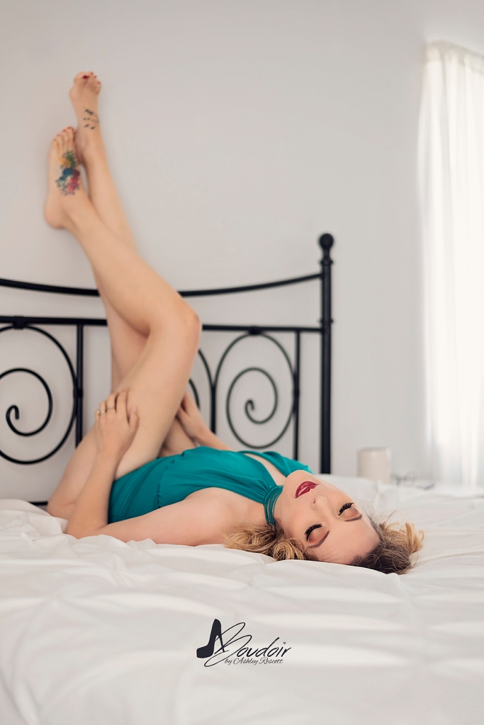 woman lying in bed with legs on wall