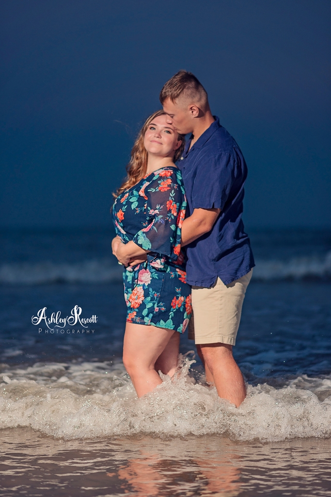 couple standing in waves at beach after sunset